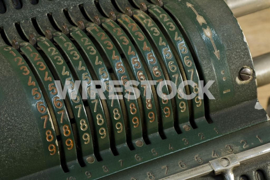 A closeup of an old pinwheel calculator under the lights with a blurry background