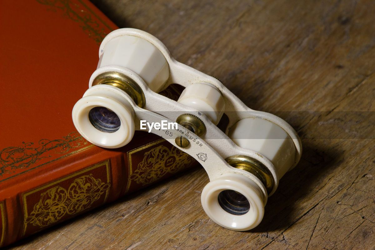 EyeEm - Antique theater binoculars on top of book on a wooden table in an antique shop
